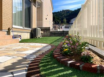 砕石・人工芝を敷、駐車スペースを増設した事で、草取りから解放され、シンボルツリーや花壇のお花で季節が感じられる空間になりました。家の外観とフェンスの感じがとてもよく遠くから見ても可愛いお家になりました。